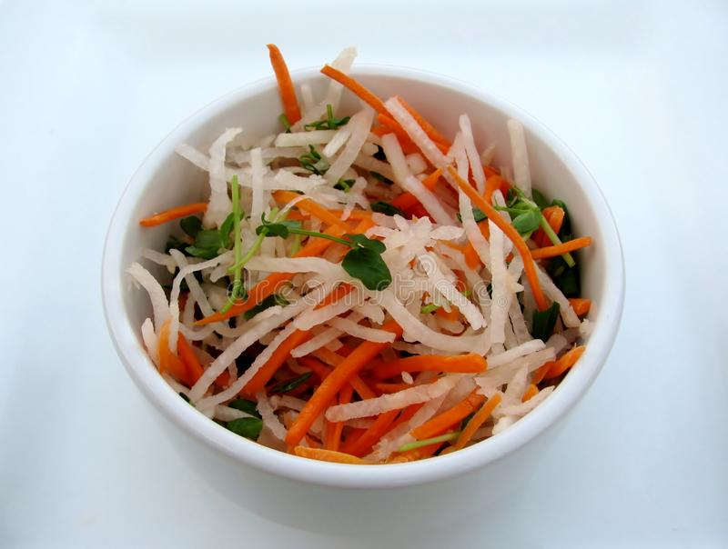 Daikon and carrot slaw salad in a white bowl. stock images