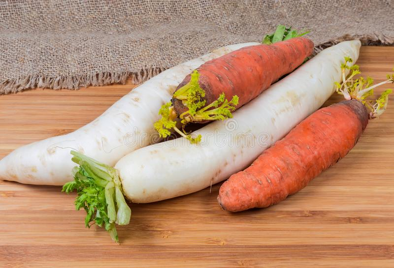 Daikon radish and carrot on wooden surface with sackcloth royalty free stock images