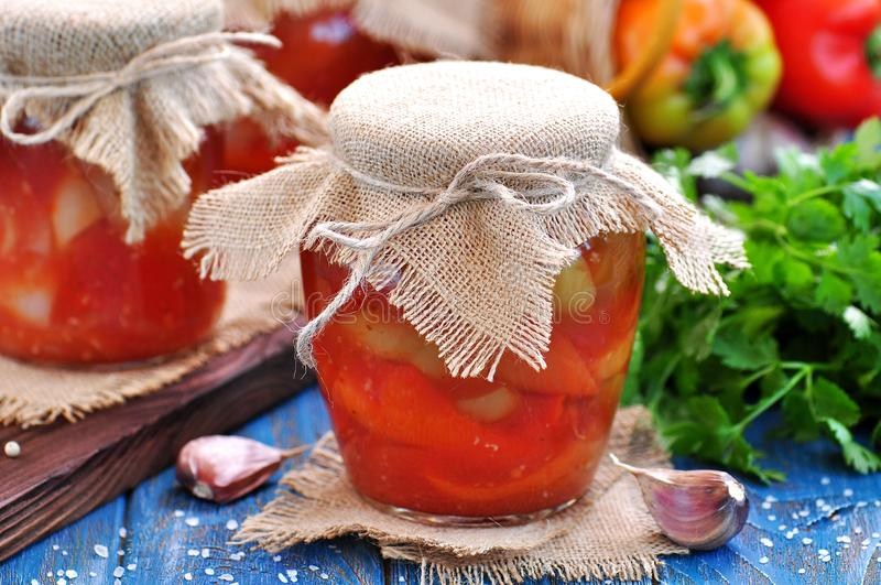 Pickled peppers in tomato juice with onions, garlic and basil. royalty free stock photography