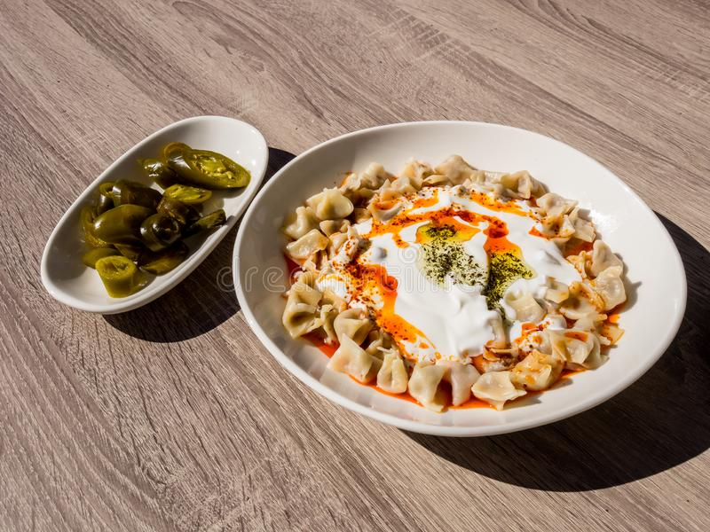 Turkish Manti with green hot pickled peppers, tomato sauce, yogurt and mint. Plate of traditional Turkish food. Top view stock photography